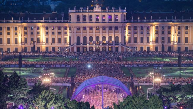 epa05331125 Schoenbrunn Palace is illuminated as the Vienna Philharmonic Orchestra performs the 'Summer Night Concert' in Vienna, Austria, 26 May 2016. Every year, around 100,000 people attend the popular open-air concert with free admission at Schoenbrunn Palace and its Baroque gardens, a UNESCO world cultural heritage site.  EPA/LISI NIESNER