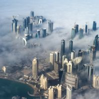 epa06011227 (FILE) - An aerial view of high-rise buildings emerging through fog covering the skyline of Doha, as the sun rises over the city, in Doha, Qatar, 15 February 2014 (reissued 05 June 2017). According to media reports, Egypt, Saudi Arabia, Bahrain and the United Arab Emirates cut off diplomatic ties with Qatar on 05 June 2017, accusing Qatar of supporting terrorism.  EPA/YOAN VALAT