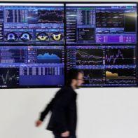 A man walks past screens displaying market data at CMC Markets in London, Britain, January 16, 2019. REUTERS/John Sibley