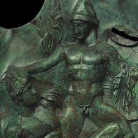 Εικόνες πολέμου. Εθνικό Αρχαιολογικό Μουσείο, αρ. ευρ. Καρ 166. Χάλκινη παραγναθίδα κράνους με ανάγλυφη σκηνή μάχης.  Από τη Δωδώνη. Τέλη 5ου-αρχές 4ου αι. π.Χ.