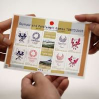 Employees of Japan Post Co. Ltd. show off the sheet of commemorative stamps for Tokyo 2020 Olympic and Paralympic Games, featuring the Olympic and Paralympic mascots Miraitowa and Someity as well as the image of the new Olympic Stadium, in Tokyo, Japan March 5, 2019. Picture taken March 5, 2019.  REUTERS/Issei Kato