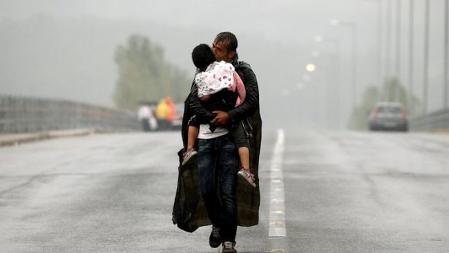 "FILE PHOTO: A Syrian refugee kisses his daughter as he walks through a rainstorm towards Greece's border with Macedonia, near the Greek village of Idomeni, September 10, 2015. REUTERS/Yannis Behrakis/File photo    SEARCH ""YANNIS BEHRAKIS"" FOR THIS STORY. SEARCH ""WIDER IMAGE"" FOR ALL STORIES.   TPX IMAGES OF THE DAY"